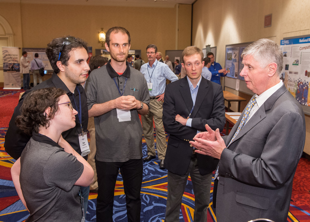 DOE NNSA's Don Cook (right) welcomed fellows, alumni and friends to the 2013 DOE laboratory poster session.